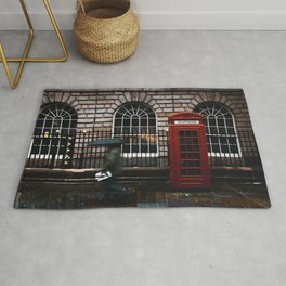 TIME LAPSE PHOTOGRAPHY OF WOMAN WALKING ON STREET WHILE HOLDING UMBRELLA NEAR LONDON TELEPHONE BOOTH BESIDE WALL Rug