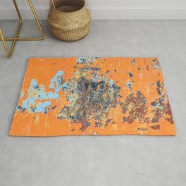 Orange metal background with cracked, peeling paint with stains of blue paint and rust spots. Rug
