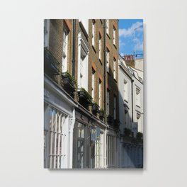 A view along sunlit brick shop fronts with shadows on a street near Covent Garden in London, UK Metal Print
