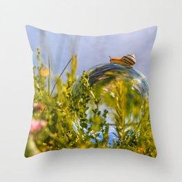 A snail crawls over a lensball Throw Pillow